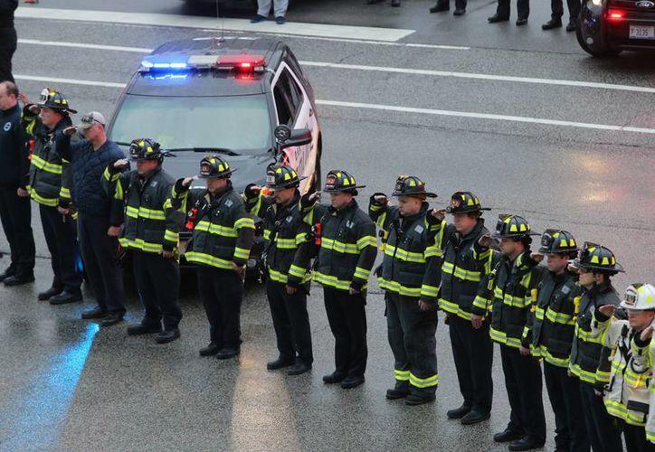 Bomberos de Chicago rinden honores a Daniel Capuano, un bombero que murió tras caer por el canal de un elevador cuando batallaba contra un incendio en el sur de Chicago. (Agencias)