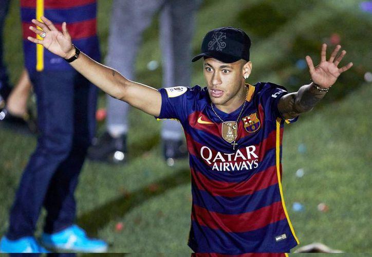 El delantero brasileño del FC Barcelona Neymar Jr., quien continuará en el equipo español durante los próximos 5 años, saluda a la afición durante un partido. (EFE/Archivo)