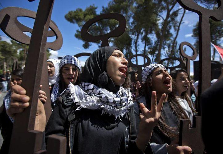 Jóvenes palestinas sostienen réplicas de llaves a gran escala, que representan los desahucios a los que han sido sometidos los palestinos. (EFE)