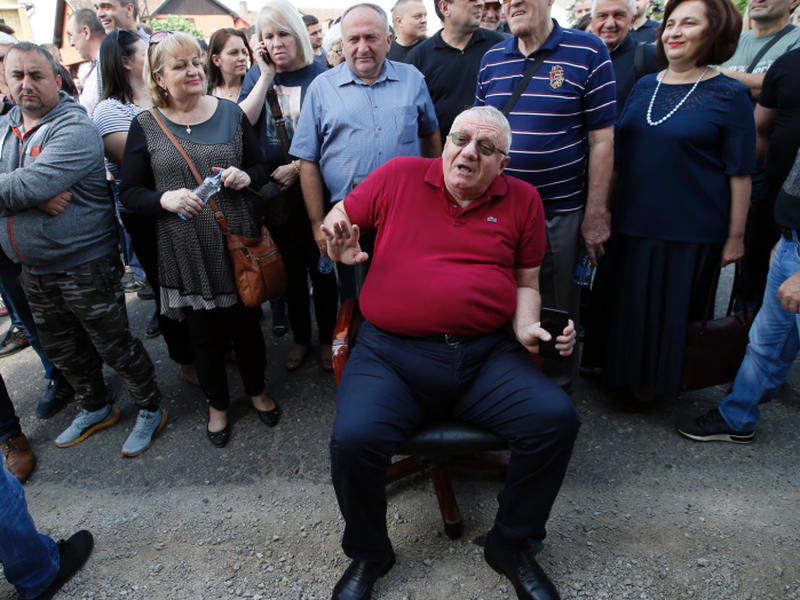 Serbian radical Party leader Vojislav Seselj sits on the road in front of a police cordon, in the village of Jarak, Serbia. (AP)