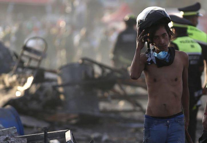 Un muchacho se quita el casco mientras hace una pausa en los trabajos de búsqueda en el mercado de fuegos artificiales de San Pablito, en Tultepec. (AP/Eduardo Verdugo)