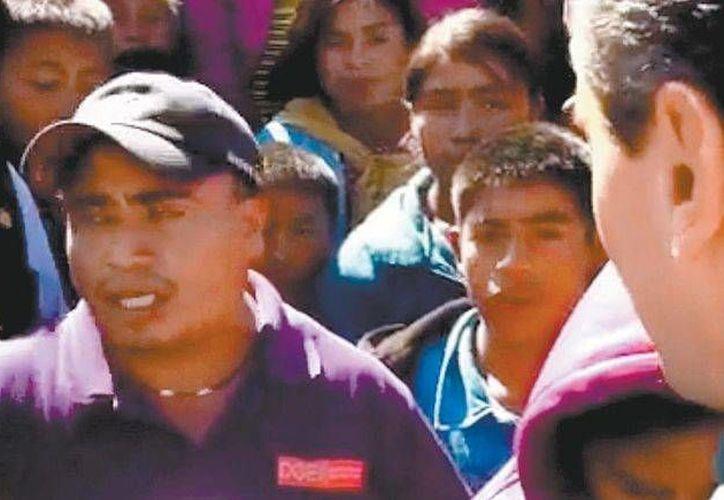 Cuando los elementos de seguridad del presidente Enrique Peña ya comenzaban a retirar a un maestro (i), Peña Nieto se puso a platicar con él. (Foto especial)