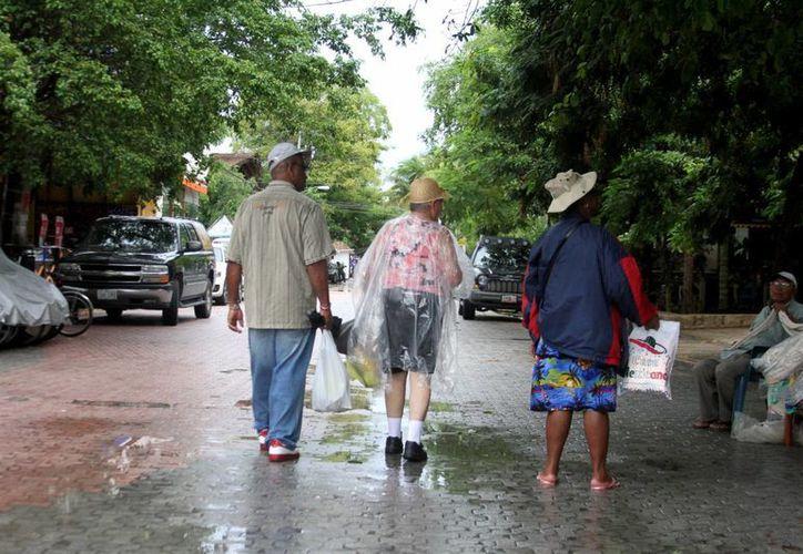 Ataviados con impermeables recorrieron el centro los pocos turistas que se animaron a salir bajo la lluvia ayer. (María Mauricio/SIPSE)