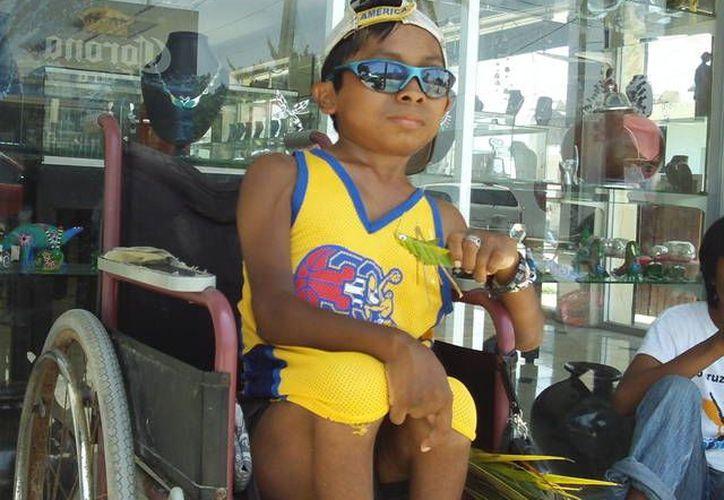 Manuelito elabora grillos de palma que vende a turistas en Progreso. (Manuel Pool/SIPSE)