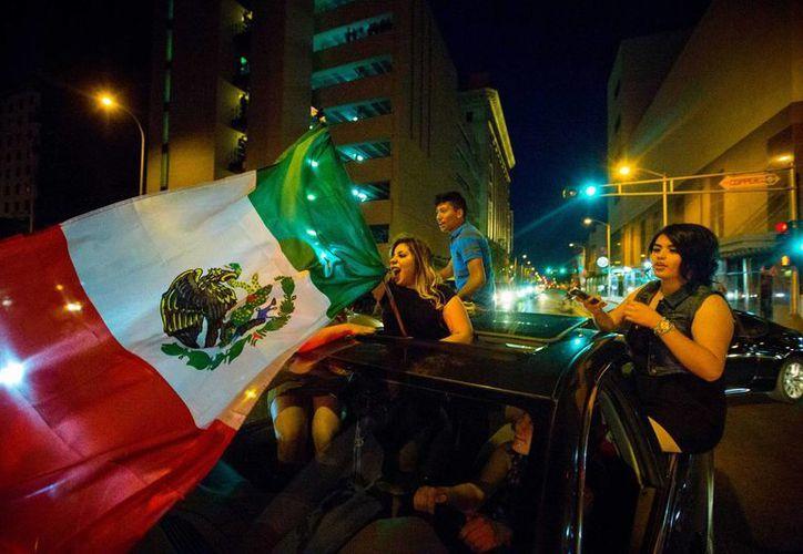 Una mujer ondeando la bandera mexicana frente al Centro de Convenciones de Albuquerque, en Nuevo México, tras un evento de campaña de Donald Trump. (Agencias)