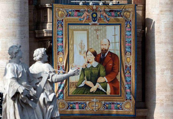 Una imagen de Louis y Zelie Martin, primer matrimonio de la era moderna canonizado por el Papa, pende de una pared exterior de la Basílica de San Pedro. Son los padres de Santa Teresita del Niño Jesús. (AP)
