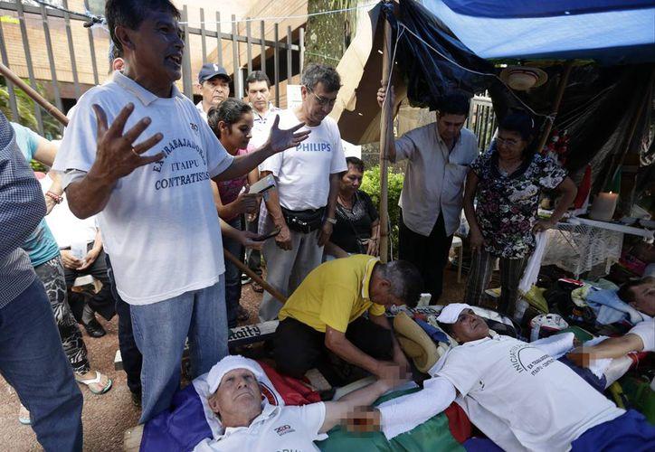 La mano de Pablo Garcete, un paraguayo de 71 años exobrero de la hidroeléctrica Itaipú, es clavada a un madero en cruz frente a la embajada de Brasil en Asunción. (Agencias)