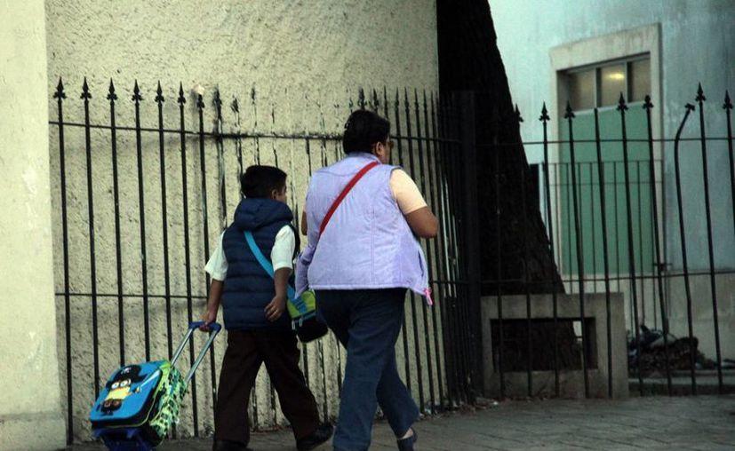 El secretario de Educación, Raúl Godoy Montañez, informó que un total de 543 colegios participan en el plan Escuelas de Tiempo Completo. Imagen de una mujer que lleva a la escuela a un menor. (Milenio Novedades)