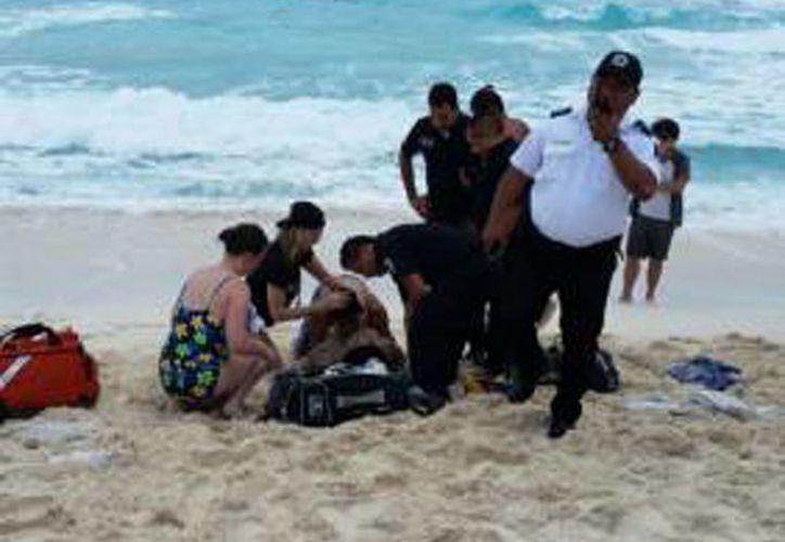 La mujer fue auxiliada por personal de Protección Civil en playa Delfines. (Redacción/SIPSE)