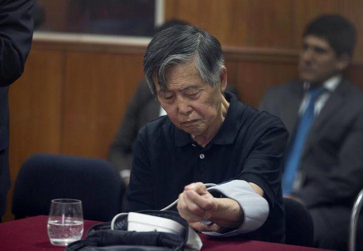 Alberto Fujimori se toma la presión en un momento de la audiencia celebrada ayer en un sala de la cárcel donde se encuentra. (Agencias)