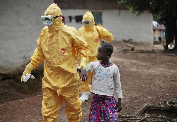 Una niña es llevada a una ambulancia después de mostrar signos de ébola en el pueblo de Freeman Reserva, a unos 30 kilómetros al norte de Monrovia, Liberia. (Agencias)