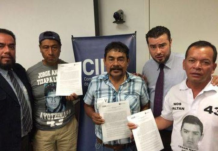 Padres de los 43 normalistas de Ayotzinapa con el documento de la CIDH que acredita el mecanismo de seguimiento en el caso Iguala. (Milenio)