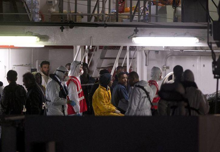 Sobrevivientes de un barco que naufragó frente a las costas de Libia el sábado esperan para desembarcar de un barco de la guardia costera italiana, el Bruno Gregoretti, en el puerto de Catania, Italia. (Foto AP/Alessandra Tarantino)