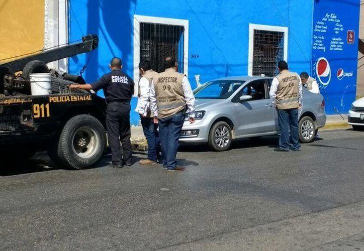 Miembros de la Dirección de Transporte inspeccionan la detención del automóvil perteneciente a la plataforma de servicios privados. (Katia Leyva/Milenio Novedades)