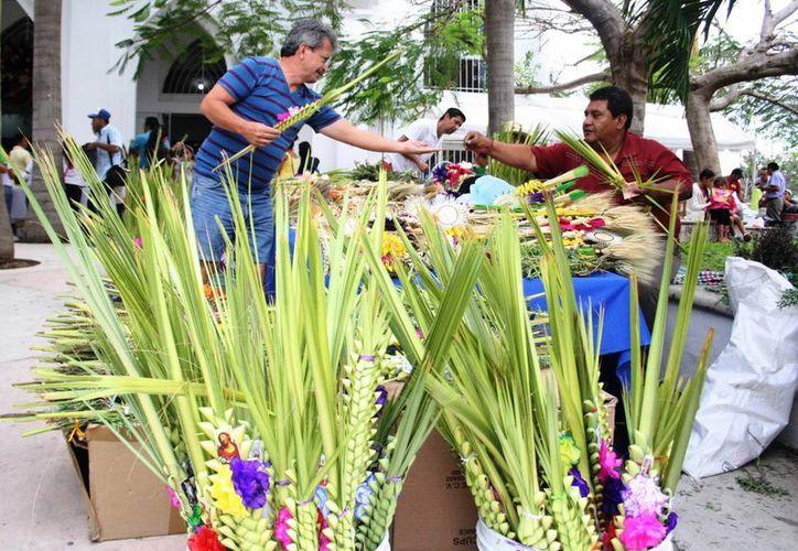 Los vendedores elaboran las palmas que se utilizarán en la misa del domingo para bendecirlas. (Octavio Martínez/SIPSE)