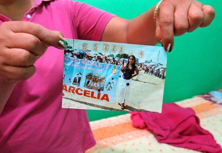 La mujer muestra la foto de su hija Erika Gómez González, quien fue asesinada por elementos del Ejército en Tlatlaya, Estado de México. (Agencias)