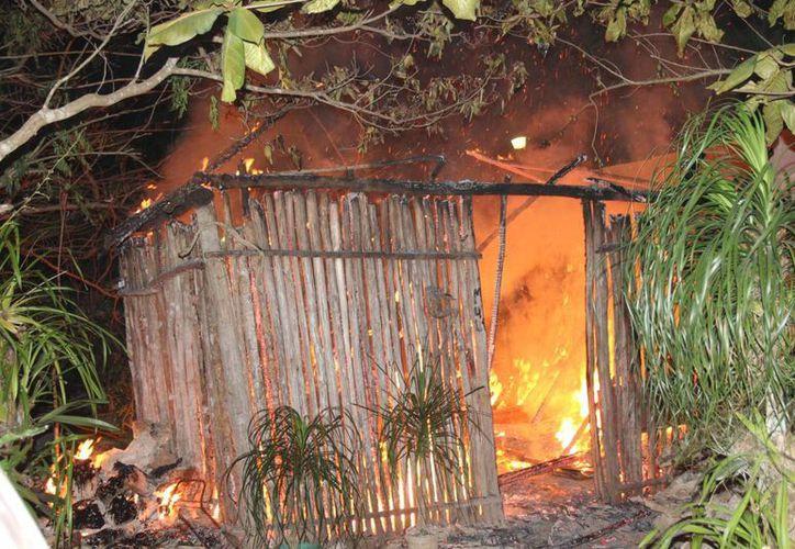 Vecinos del solitario sexagenario y Bomberos trataron sin éxito de apagar el fuego que se propagó con la fuerza de los vientos. (Manuel Salazar/SIPSE)