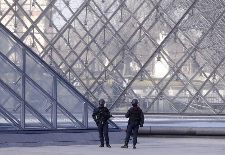 Agentes de policía patrullan junto a la pirámide en el exterior del museo del Louvre en París. (AP/Thibault Camus)