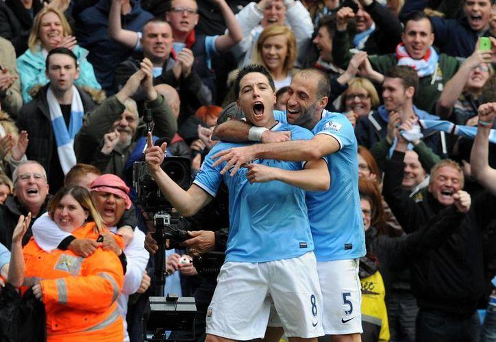 Samir Nasri (i) celebra con Pablo Zabaleta el segundo gol que dio el triunfo al Manchester City sobre el West Ham en la final de la Liga Premier de Inglaterra. (AP)