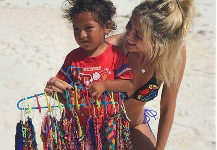 La modelo argentina subió un par de fotografías en las que aparece junto a un niño que vende pulseritas. (Foto: Instagram)