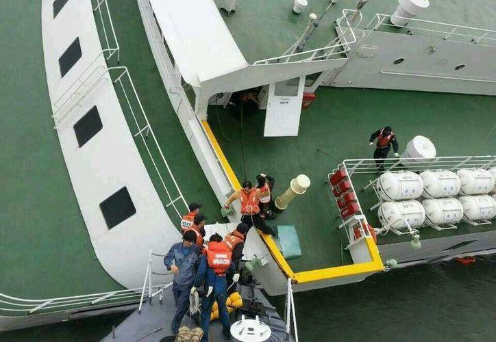 """Foto del Servicio de Guardacostas surcorano proporcionada hoy, que muestra al capitán del buque Sewol, Lee Jun-Seok (3º dcha), mientras recibe ayuda de la policía marítima para abandonar el barco durante el naufragio del buque """"Sewol"""". (EFE/Servicio de Guardacostas surcoreano.)"""