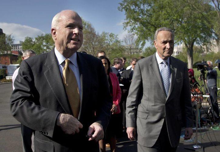 El senador republicano John McCain (izquierda) y el senador demócrata Charles Schumer hablan con representantes de los medios de comunicación fuera de la Casa Blanca. (Agencias)