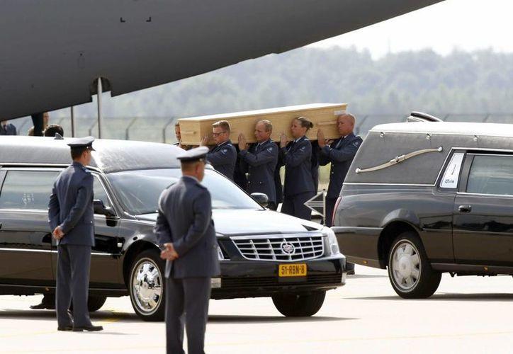 La recuperación de cuerpos tras el avionazo de Malaysian Airlines fue toda una odisea debido a que el aparato cayó en una zona de conflicto. En la foto, traslado de féretros en el aeropuerto de Eindhoven. (EFE)