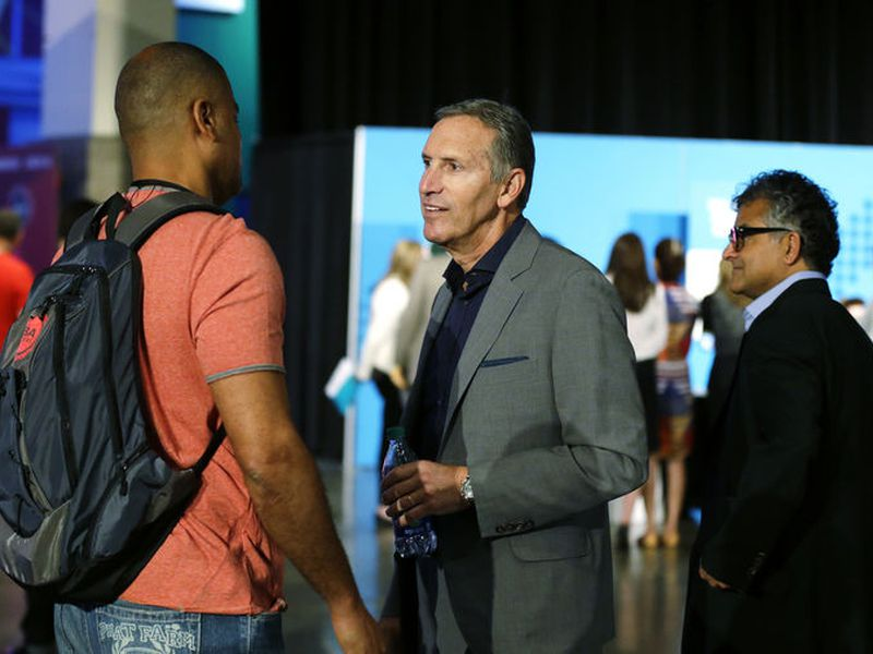Howard Schultz, center, CEO of Starbucks Corp., talks with an an attendee at a job fair in Seattle sponsored by the 100,000 Opportunities Initiative.