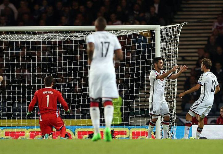 El alemán Ilkay Gundogan (segundo desde la derecha), celebra el gol que le anotó a Escocia y que contribuyó a la victoria germana por 3-2 como visitante en partido de eliminatoria de la Eurocopa. (Foto: AP)
