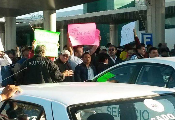 Imagen de los taxistas durante el bloqueo al  aeropuerto internacional de Mérida Manuel Crescencio Rejón. (Milenio Novedades)