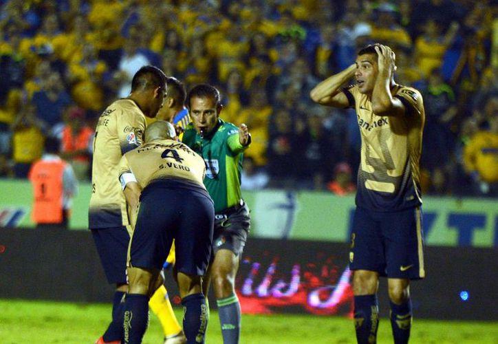 Momento en que el árbitro José Alfredo Peñaloza marca un penal que se convirtió en el primero de los tres goles que Tigres le marcó a Pumas en el primer partido de la final del futbol mexicano. (Notimex)