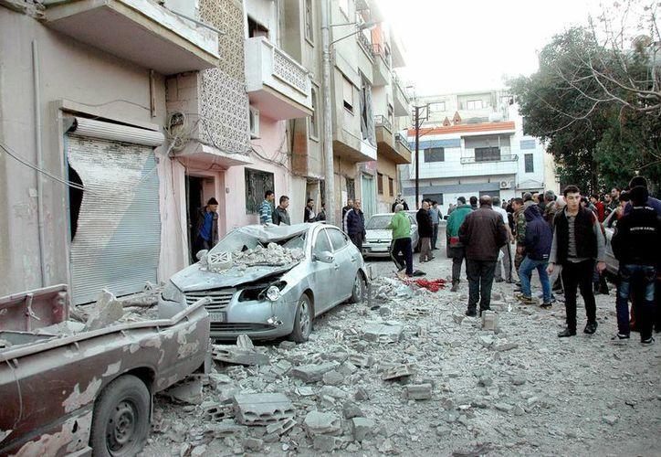 Sirios inspeccionando los daños causado por proyectiles de cohetes , supuestamente lanzados ayer por grupos rebeldes en los barrios Akremah y al-Abbasiye en Homs, Siria. (EFE)