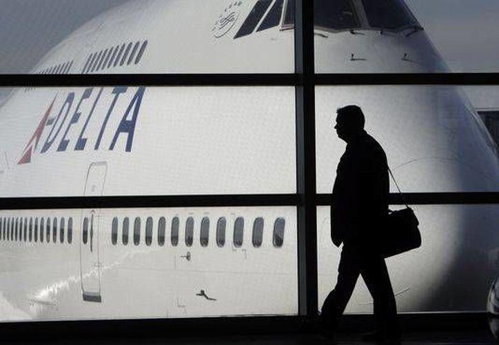Foto de archivo en la que se ve que a un pasajero pasar junto a un Delta Air Lines Boeing 747 en el aeropuerto de Detroit Metropolitan Wayne County. (Foto de contexto/Agencias)