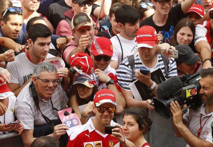 El piloto alemán de Ferrari Sebastian Vettel posa para una foto con seguidores en el circuito de Montmeló, a las afueras de Barcelona, España. (Agencias)