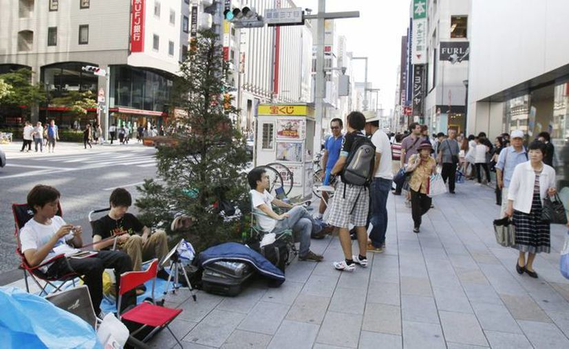 Japoneses se forman sentados en una tienda de Apple en Tokio. (Agencias)