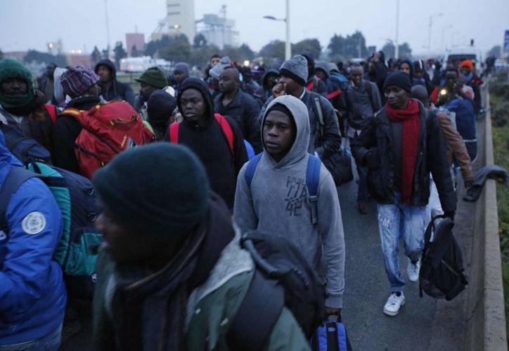 Migrantes esperando a registrarse en un centro de procesamiento en el campo improvisado conocido como 'La Jungla', cerca de Calais. (AP/Emilio Morenatti)