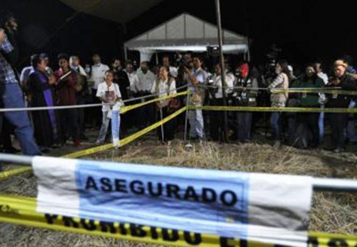 Los peritos aseguran que familiares han invadido la zona donde se encuentran los restos de unas 100 personas en el poblado de Tetelcingo. (Excélsior)