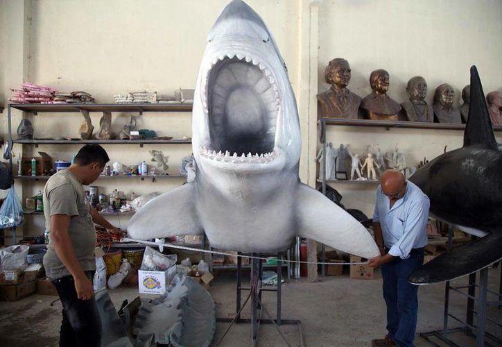 """""""Paccelli"""" da los últimos toques a un tiburón, una de las figuras que los visitantes podrán admirar en el Paseo Verde. (Milenio Novedades)."""