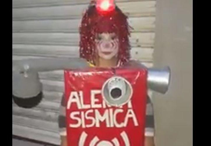 """El traje del menor está compuesto de una caja forrada con papel rojo, en la que se lee """"Alerta sísmica"""". (Foto: Captura)"""