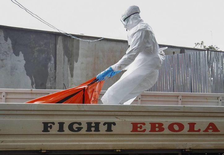Un trabajador sanitario de Liberia con una víctima de ébola en el centro de tratamiento en Monrovia. (Archivi/EFE)