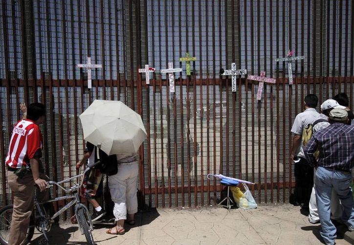 Migrantes deportados intentan contactar al grupo Ángeles de la Frontera y abogados especialistas en Inmigración, a través de la malla metálica del Parque de la Amistad, en Tijuana, BC. (Archivo/Notimex)