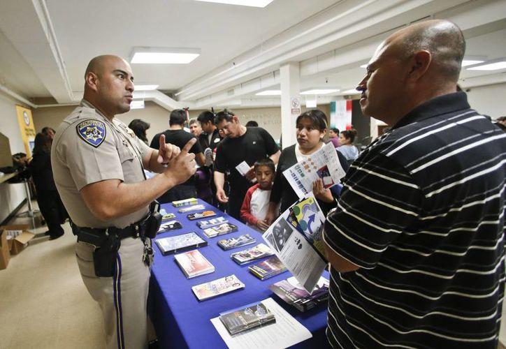 En esta imagen de archivo tomada el 23 de abril de 2014, el agente de la patrulla de carreteras de California Armando García explica a inmigrantes el proceso para obtener un permiso de conducir durante una sesión informativa en el consulado mexicano, en San Diego, California. (Agencias)