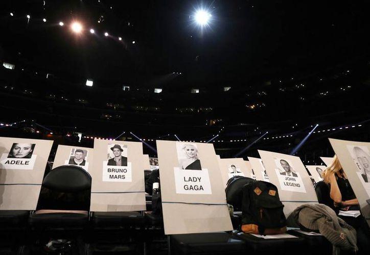 En el Stapless Center, ya se observan las pancartas que determinan los lugares que ocuparán los artistas y famosos asistentes a la ceremonia 59 de los Grammy. Por primera vez, un hombre y una mujer transgénero entregarán galardones. (AP)