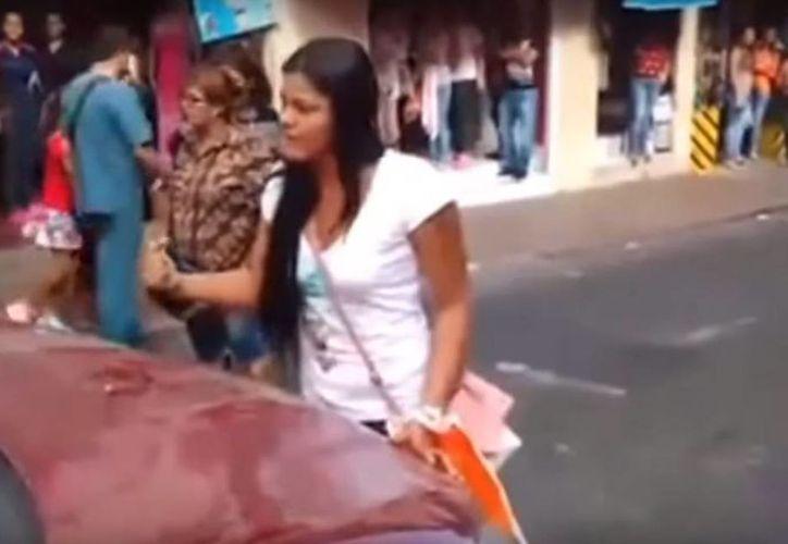 Al final, la mujer celosa logró que la 'otra' bajara del carro de su esposo. (Captura de pantalla/YouTube)