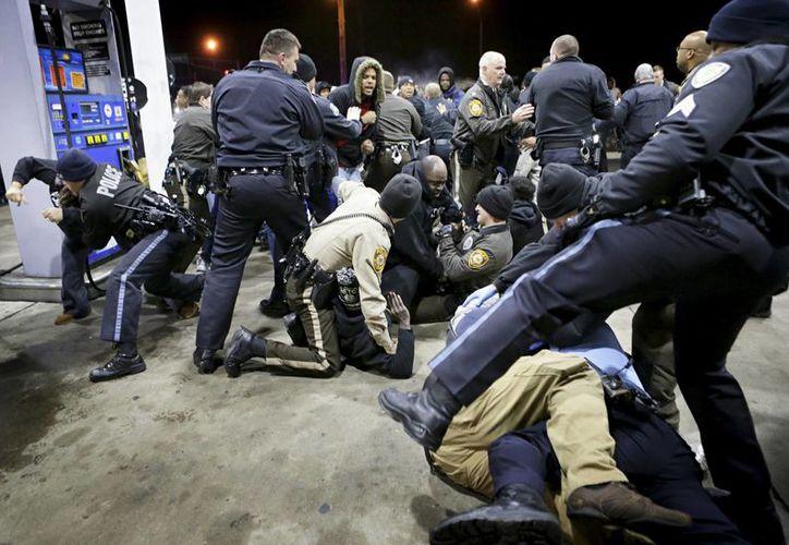 La policía trata de contener a una multitud el miércoles 24 de diciembre de 2014 en una gasolinera tras un tiroteo el martes en Berkeley, Missouri. (Foto AP/St. Louis Post-Dispatch, David Carson)