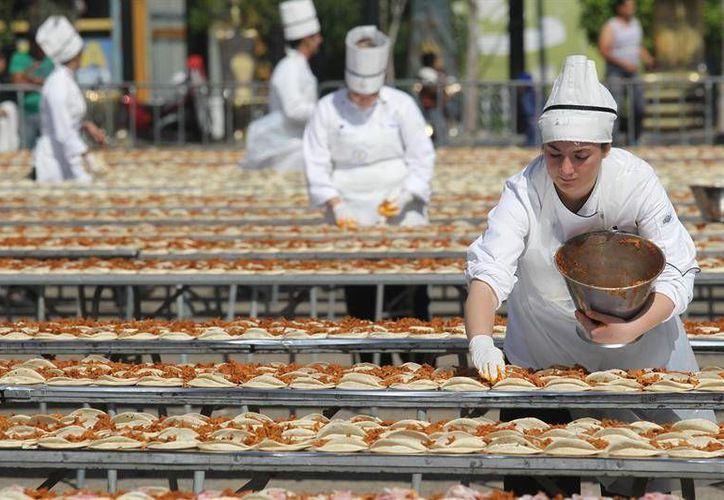 Se requirieron las manos de 200 chefs para preparar el taco de cochinita pibil más largo del mundo. (EFE)