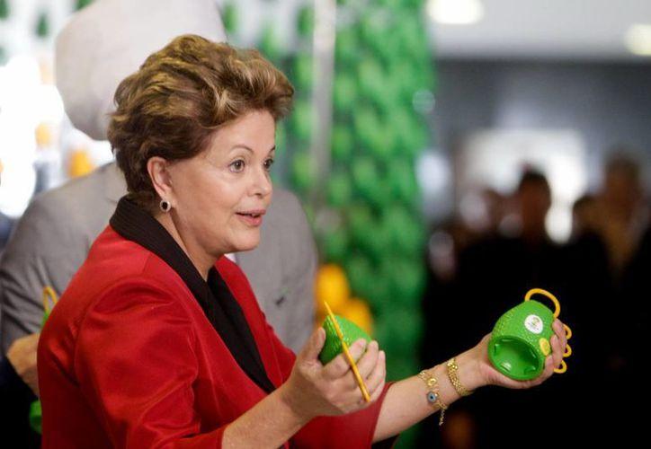 La mandataria brasileña, Dilma Rousseff, sostiene unas 'caxirolas' (especie de maraca diseñada como respuesta brasileña a la atronadora 'vuvuzela' sudafricana). (EFE/Archivo)