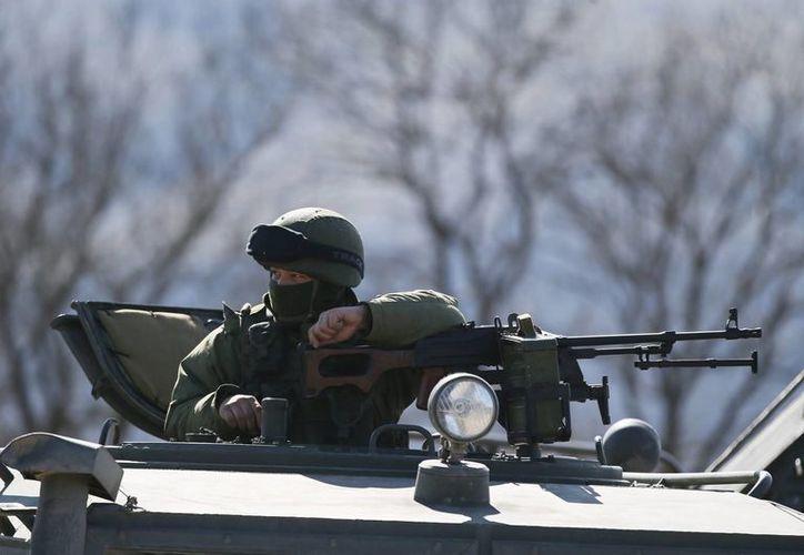 Un militar armado hace guardia en la base militar ucraniana en la localidad de Pereválnoye, a las afueras de Simferópol, Crimea, Ucrania. (EFE)