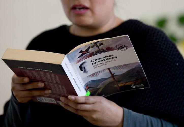 Un fan del escritor Gabriel García Márquez lee su obra cumbre 100 años de soledad en una biblioteca de la Ciudad de México. Gabo falleció hace un años. (Foto: AP)