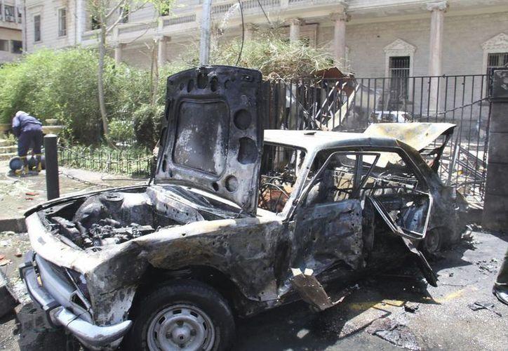 Vista de un vehículo calcinado tras la explosión de un coche bomba en el centro de Damasco, Siria. (Archivo/EFE)